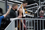 Loyola of Chicago head coach Porter Moser walks off the court with Lucas Williamson after beating Illinois in a college basketball game in the second round of the NCAA tournament at Bankers Life Fieldhouse in Indianapolis Sunday, March 21, 2021. Loyola upset Illinois 71-58. (AP Photo/Mark Humphrey)