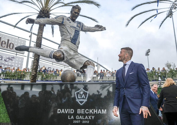 Former LA Galaxy MLS soccer midfielder David Beckham looks at a statue of himself at Legends Plaza in front of Dignity Health Sports Park in Carson, Calif., Saturday, March 2, 2019. (AP Photo/Ringo H.W. Chiu)