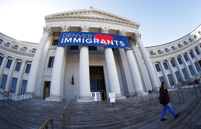 FILE - In this Feb. 26, 2018 file photo, a banner to welcome immigrants is viewed through a fisheye lens over the main entrance to the Denver City and County Building inDenver. U.S. Immigration and Customs Enforcement has subpoenaed Denver law enforcement for information on four foreign nationals wanted for deportation and could expand the unusual practice to other cities, an escalation of the conflict between federal officials and so-called sanctuary cities. And if the city officials don't respond, ICE, the Homeland Security agency responsible for arresting and deporting people in the U.S. illegally, could take the subpoena to a federal judge who can order compliance, and find them in contempt.  (AP Photo/David Zalubowski, File)