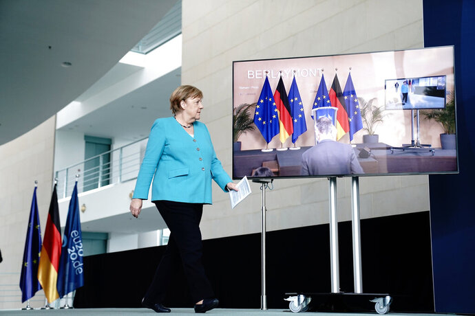 Germany's Chancellor Angela Merkel  walks, prior to a joint press conference with EU Commission President Ursula von der Leyen via videolink, in the foyer of the Federal Chancellery, in Berlin, Thursday, July 2, 2020. Merkel joined the President of the EU Commission, the three executive Vice-Presidents, the Commissioner for External Relations and the Commissioner for Internal Affairs to discuss the work programme as Germany took over the presidency of the Council of the EU. (Kay Nietfeld/dpa via AP)