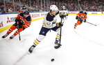Buffalo Sabres' Brandon Montour (62) is chased by Edmonton Oilers' James Neal (18) during the second period of an NHL hockey game, Sunday, Dec. 8, 2019 in Edmonton, Alberta. (Jason Franson/The Canadian Press via AP)