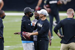 An unmasked New Orleans Saints quarterback Drew Brees, right, greets a masked Carolina Panthers quarterback Teddy Bridgewater before an NFL football game in New Orleans, Sunday, Oct. 25, 2020. (AP Photo/Brett Duke)