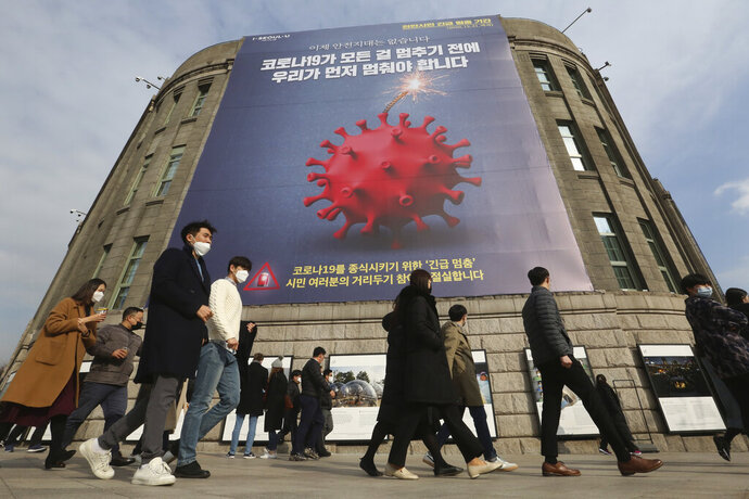 People wearing face masks as a precaution against the coronavirus walk under a banner emphasizing an enhanced social distancing campaign in front of Seoul City Hall in Seoul, South Korea, Wednesday, Nov. 25, 2020. The banner reads: