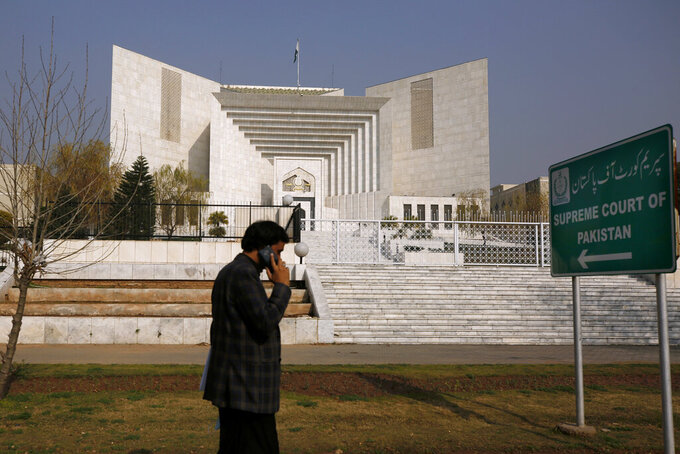 A Pakistani walks past the Supreme Court building in Islamabad, Pakistan, Wednesday, Feb. 10, 2021. In a landmark ruling, Pakistan's top court on Wednesday commuted the death sentences of two mentally ill prisoners who have spent decades on death row, the first such ruling in this conservative Muslim-majority nation. (AP Photo/Anjum Naveed)