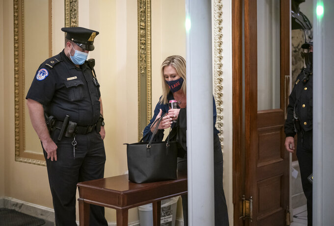 Rep. Marjorie Taylor Greene, R-Ga., an ally of President Donald Trump, passes through a metal detector before entering the House chamber, a new security measure put into place after a mob stormed the Capitol, in Washington, Tuesday, Jan. 12, 2021. The House is trying to push the vice president and Cabinet to act even more quickly to remove President Donald Trump from office. Democrats are set to pass a resolution calling on Vice President Mike Pence to invoke constitutional authority under the 25th Amendment to oust Trump. (AP Photo/J. Scott Applewhite)