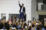 Opposition leader Juan Guaido waves to supporters during a rally at Bolivar Plaza in Chacao,  a municipality of Caracas, Venezuela, Tuesday, Feb. 11, 2020. Guaido returned home from a tour of nations that back his effort to oust socialist leader Nicolas Maduro. (AP Photo/Ariana Cubillos)