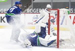 Vancouver Canucks goalie Braden Holtby stops Toronto Maple Leafs' Wayne Simmonds, back right, as Vancouver's Travis Hamonic, back left, watches during the third period of an NHL hockey game in Vancouver, British Columbia, Sunday, April 18, 2021. (Darryl Dyck/The Canadian Press via AP)