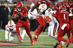 Louisville quarterback Micale Cunningham (3) runs from the attempted tackle of Syracuse linebacker Lakiem Williams (46) during the first half of an NCAA college football game in Louisville, Ky., Saturday, Nov. 23, 2019. (AP Photo/Timothy D. Easley)