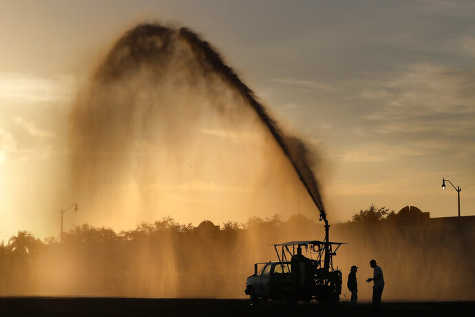 In this Monday, Oct. 28 2019, photo, a farm is watered in Florida City, Fla, just east of the main entrance to Everglades National Park. Early settlers and developers dredged and drained much of the ecosystem for agriculture. (AP Photo/Robert F. Bukaty)