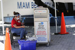 FILE - In this Aug. 7, 2020, file photo, a poll worker wears a protective shield and mask as a precaution against the coronavirus as she monitors a ballot drop box, identified in English, Spanish and Haitian Creole, for mail-in ballots outside of a polling station during early voting in Miami Beach, Fla. Getting enough people to staff polling places amid the pandemic is a challenge in many states. The virus' disproportionate impact on Latinos has made the task of recruiting Spanish-speakers even more difficult. (AP Photo/Lynne Sladky, File)