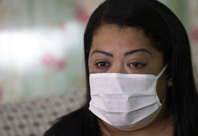 """Nurse Lidiane Melo cries during an interview with The Associated Press at her home in Rio de Janeiro, Brazil, Wednesday, April 14, 2021. In the early days of the pandemic, as sufferers were calling out for comfort that she was too busy to provide, Melo filled two rubber gloves with warm water, knotted them shut, and sandwiched them around a patient's hand, to re-create a loving clasp. Some have christened the practice the """"hand of God,"""" and it is now the searing image of a nation roiled by a medical emergency with no end in sight. (AP Photo/Silvia Izquierdo)"""
