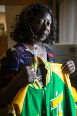 Gayle Tart, an attorney in Gulfport and a 33rd Ave. School alumna, poses for a portrait with the letterman jacket of Jimmie Woullard at East Biloxi, Miss., Library on Saturday, July 31, 2021. (Hannah Ruhoff/The Sun Herald via AP)
