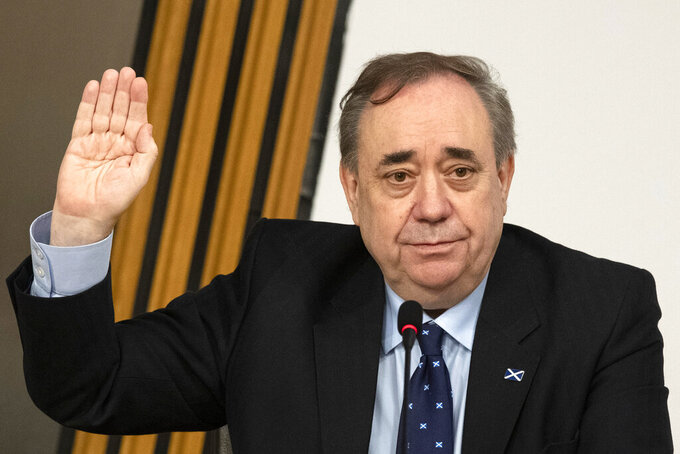 Former Scottish leader Alex Salmond is sworn in before giving evidence to a committee of the Scottish parliament at Holyrood in Edinburgh, Friday Feb. 26, 2021. Former Scottish leader Alex Salmond will lay out his belief that his successor tried to damage his reputation through an unfair probe of sexual harassment allegations when he appears before lawmakers Friday in a case that is tearing apart the country's biggest political party. (Andy Buchanan/Pool via AP