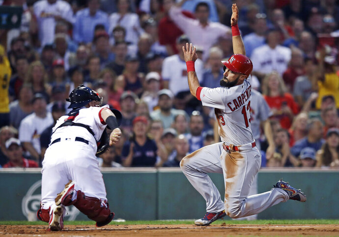 FILE - In this Aug. 16, 2017, file photo, St. Louis Cardinals' Matt Carpenter, right, tries unsuccessfully to avoid a tag by Boston Red Sox catcher Christian Vazquez during the second inning of a baseball game in Boston. The Cardinals and the Red Sox would have had one of their rare regular-season series this week. They have met in four different World Series. They would have played a three-game series at Fenway Park this week if not for the coronavirus pandemic. (AP Photo/Charles Krupa, File)
