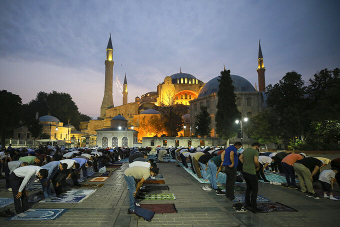 Muslims offer prayers during the first day of Eid al-Adha, outside the iconic Haghia Sophia in the historic Sultan Ahmed district of Istanbul, Tuesday, July 20, 2021. Thousands of Muslims attended dawn Eid al-Adha prayers in Istanbul. (AP Photo/Mucahid Yapici)