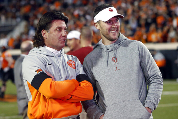 FILE - In this Nov. 30, 2019, file photo, Oklahoma State coach Mike Gundy, left, talks with Oklahoma coach Lincoln Riley before an NCAA college football game in Stillwater, Okla. The teams meet this week in the Bedlam game. (AP Photo/Sue Ogrocki, File)