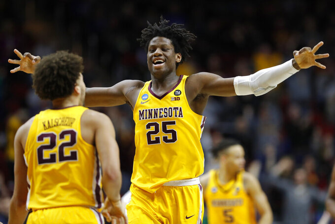 Minnesota center Daniel Oturu (25) celebrates with teammate Gabe Kalscheur (22) during a first round men's college basketball game against Louisville in the NCAA Tournament, Thursday, March 21, 2019, in Des Moines, Iowa. (AP Photo/Charlie Neibergall)