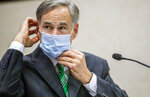 CORRECTS CITY TO AUSTIN, INSTEAD OF HOUSTON Texas Gov. Greg Abbott adjusts his mask after giving an update on the categories of medical surge facilities and how it effects Level 5 of maintaining staffed beds during a press conference at Texas Department of Public Safety, Tuesday, June 16, 2020, in Austin, Texas. (Ricardo B. Brazziell/Austin American-Statesman via AP)