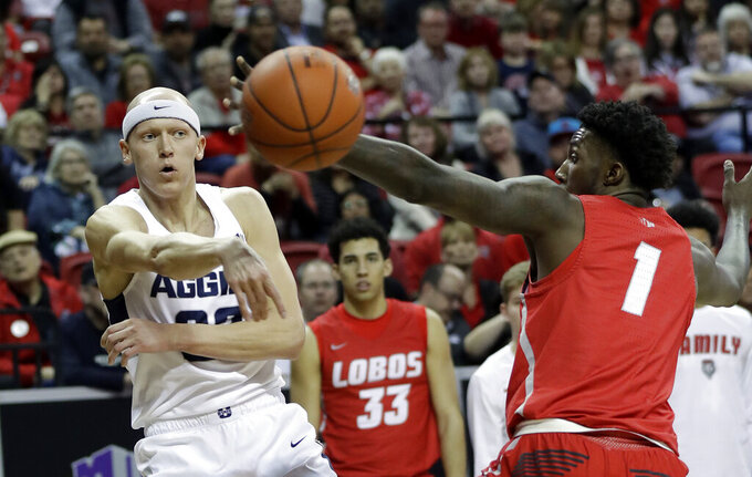 Utah State's Brock Miller passes the ball around New Mexico's Jalen Harris (1) during the first half of an NCAA college basketball game in the Mountain West Conference men's tournament Thursday, March 14, 2019, in Las Vegas. (AP Photo/Isaac Brekken)