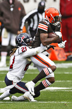 Cleveland Browns wide receiver Rashard Higgins (82) is tackled by Houston Texans cornerback Bradley Roby (21) during the first half of an NFL football game, Sunday, Nov. 15, 2020, in Cleveland. (AP Photo/Ron Schwane)