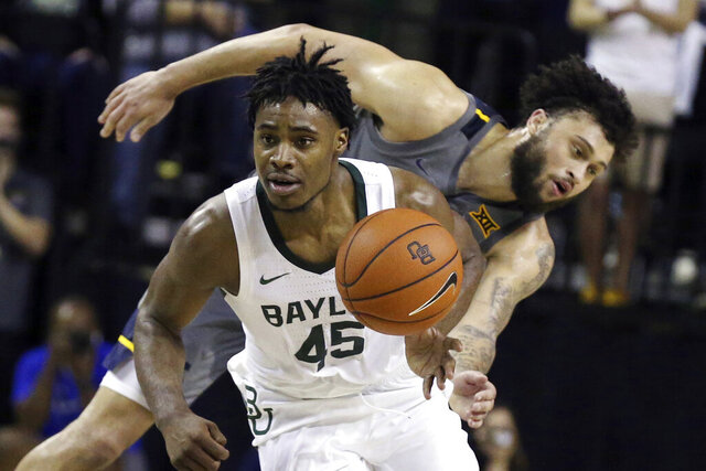 Baylor guard Davion Mitchell, left, breaks away from West Virginia guard Jermaine Haley for a fast break in the second half of an NCAA college basketball game, Saturday, Feb. 15, 2020, in Waco, Texas. (AP Photo/Rod Aydelotte)
