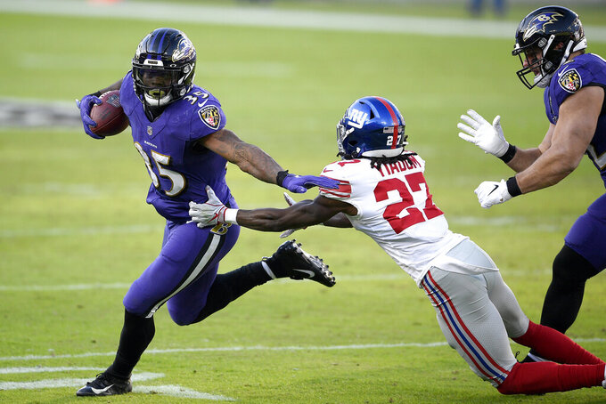 Baltimore Ravens wide receiver Marquise Brown runs with the ball as New York Giants cornerback Isaac Yiadom (27) tries to stop him during the second half of an NFL football game, Sunday, Dec. 27, 2020, in Baltimore. (AP Photo/Nick Wass)