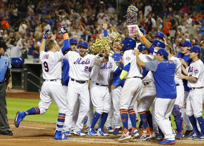 New York Mets' Brandon Nimmo (9) runs toward home plate and waiting teammates on a walk-off three-run home run during the 10th inning of a baseball game against the Philadelphia Phillies on Wednesday, July 11, 2018, in New York. The Mets won 3-0. (AP Photo/Frank Franklin II)