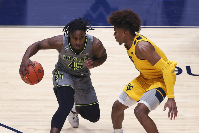 Baylor guard Davion Mitchell (45) is defended by West Virginia guard Miles McBride during the first half of an NCAA college basketball game Tuesday, March 2, 2021, in Morgantown, W.Va. (AP Photo/Kathleen Batten)