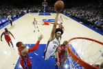 Brooklyn Nets' Jarrett Allen, center, goes up for a dunk between Philadelphia 76ers' Tobias Harris, left, and Al Horford during the first half of an NBA basketball game, Wednesday, Jan. 15, 2020, in Philadelphia. (AP Photo/Matt Slocum)
