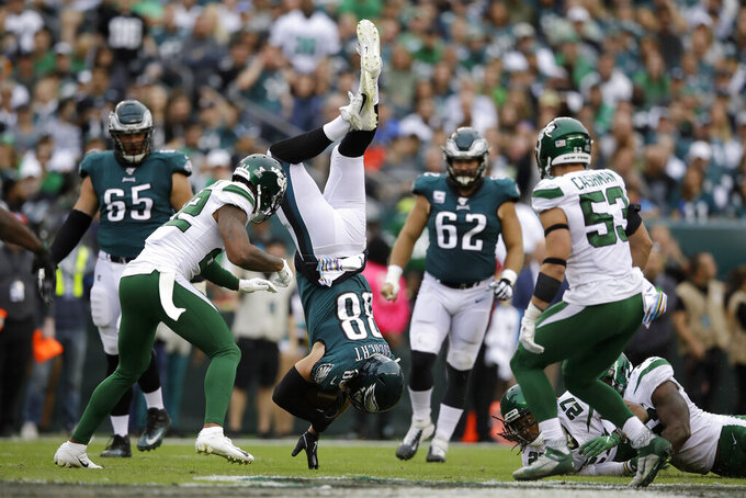 Philadelphia Eagles' Dallas Goedert (88) tumbles in front of New York Jets' Trumaine Johnson (22) and Blake Cashman (53) after trying to avoid a tackle from Neville Hewitt (46) during the first half of an NFL football game, Sunday, Oct. 6, 2019, in Philadelphia. (AP Photo/Matt Rourke)