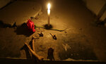 A candle burns inside an empty mausoleum at El Tejar cemetery, in downtown Quito, Ecuador, Wednesday, Sept. 11, 2019. On a recent evening, 13 visitors ventured into the cemetery, which is filled with blocks of tombs stacked four levels and higher. (AP Photo/Dolores Ochoa)