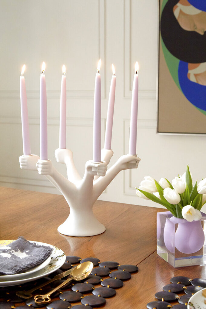 This image provided by Jonathan Adler shows a candlestick holder. Designer Jonathan Adler pays homage to Paris' Pompidou Center with a candelabra he calls Eve; a ringlet of white porcelain hands stands ready to grip tapers, like a circle of dancers. (Jonathan Adler via AP)