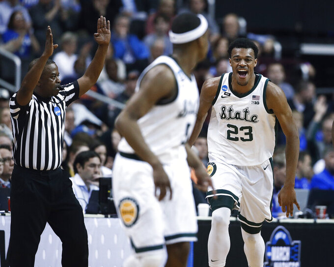 Michigan State forward Xavier Tillman (23) reacts to scoring against LSU during the first half of an East Regional semifinal in the NCAA men's college basketball tournament in Washington, Friday, March 29, 2019. (AP Photo/Patrick Semansky)
