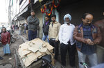 Daily laborers wait outside a market which was the scene of a devastating fire Sunday, in New Delhi, India, Monday, Dec. 9, 2019. Authorities say an electrical short circuit appears to have caused a devastating fire that killed dozens of people in a crowded market area in central New Delhi. Firefighters fought the blaze from 100 yards away because it broke out in one of the area's many alleyways, tangled in electrical wire and too narrow for vehicles to access. (AP Photo/Manish Swarup)