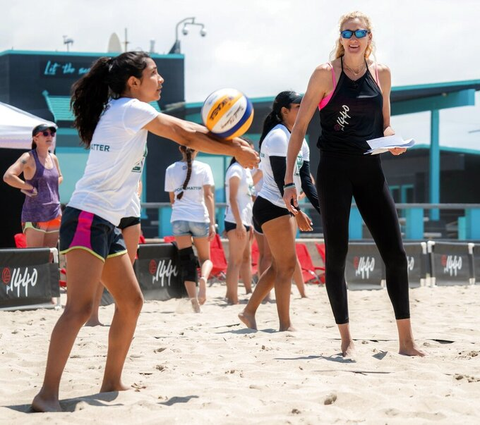 In this June 22, 2019, photo provided by p1440, volleyball star Kerri Walsh Jennings, right, teaches at a volleyball camp in Huntington Beach, Calif. Walsh Jennings has created a virtual summer camp in 2020 for young volleyball players and others seeking to stay active during the coronavirus pandemic. (Jessie Pez/p1440 via AP)