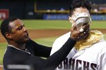 Arizona Diamondbacks' Josh Rojas, right, gets a pie in the face from Adam Jones, left, during an on-field interview after the team's baseball game against the Los Angeles Dodgers on Friday, Aug. 30, 2019, in Phoenix. Rojas had a two-run home run in the seventh as the Diamondbacks won 5-4. (AP Photo/Ross D. Franklin)