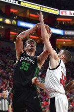 South Carolina Upstate center Nevin Zink (35) attempts a shot over the defense of Louisville guard Ryan McMahon (30) during the first half of an NCAA college basketball game in Louisville, Ky., Wednesday, Nov. 20, 2019. (AP Photo/Timothy D. Easley)