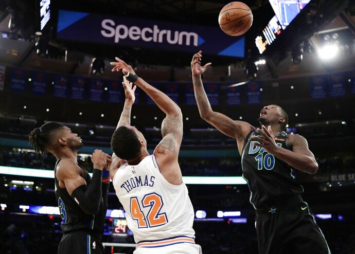 Dallas Mavericks' Dorian Finney-Smith (10) fights for control of the ball with New York Knicks' Lance Thomas (42) as teammates Nerlens Noel defends during the first half of an NBA basketball game Tuesday, March 13, 2018, in New York. (AP Photo/Frank Franklin II)