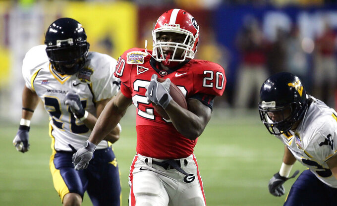 FILE - In this Jan. 2, 2006, file photo, Georgia's Thomas Brown (20) outruns West Virginia's Anthony Mims, left, and Mike Lorello, right, on a second quarter touchdown run in the Sugar Bowl football game at the Georgia Dome in Atlanta. South Carolina coach Will Muschamp brought in former Bulldogs star and assistant coach Thomas Brown to lead Gamecocks running backs this season, hopeful he can turn an area that's been near the bottom of the Southeastern Conference the past three years into one that vaults the Gamecocks into contention in the Eastern Division.  (AP Photo/Bill Haber, File)