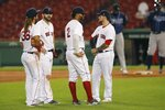 Boston Red Sox players, from left, Jonathan Arauz, Mitch Moreland, Xander Bogaerts and Michael Chavis wait on the field for a pitching change during the eighth inning of a baseball game against the Tampa Bay Rays, Tuesday, Aug. 11, 2020, in Boston. (AP Photo/Michael Dwyer)