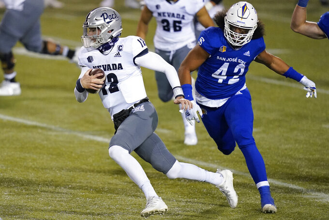 Nevada quarterback Carson Strong (12) carries past San Jose State defensive end Viliami Fehoko (42) during the first half of an NCAA college football game Friday, Dec. 11, 2020, in Las Vegas. (AP Photo/John Locher)