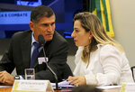 "In this April 24, 2019 handout photo, congresswoman Katia Sastre, an ally of President Jair Bolsonaro, talks with then Secretary of Government Minister Alberto dos Santos Cruz, at Congress in Brasilia, Brazil. Several weeks after publishing explosive reports on a top member of Brazil's far-right government, U.S. journalist Glenn Greenwald sat before a congressional committee as Sastre shouted; ""Who should be judged, convicted and in prison is the journalist!""(Wilson Dias/Agencia Brasil via AP)"