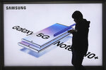 A man passes by an advertisement of Samsung Electronics' Galaxy 5G Note10+ smartphone at a subway station in Seoul, South Korea, Thursday, Oct. 31, 2019. Samsung Electronics said it operating profit for the last quarter fell by nearly 56%, with its robust sales of smartphone, displays and TVs offset by a continuously weak market for computer chips. (AP Photo/Ahn Young-joon)