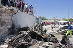 Somalis look at the wreckage after a suicide car bomb attack in the capital Mogadishu, Somalia Wednesday, May 22, 2019. A police spokesman said the attack killed at least six people and injured more than a dozen, while Islamic extremist group al-Shabab claimed responsibility for the blast, saying it targeted vehicles carrying government officials. (AP Photo/Farah Abdi Warsameh)
