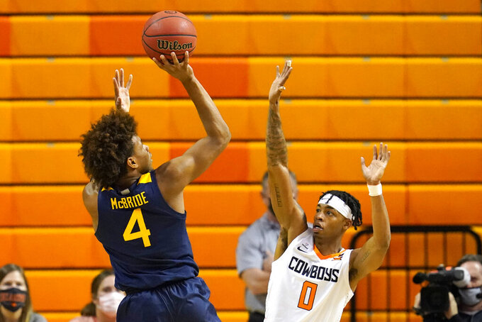 West Virginia guard Miles McBride (4) shoots over Oklahoma State guard Avery Anderson III (0) in the second half of an NCAA college basketball game Monday, Jan. 4, 2021, in Stillwater, Okla. (AP Photo/Sue Ogrocki)