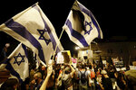 Israeli protesters wave flags, hold signs and chant slogans during a demonstration against Israeli Prime Minister Benjamin Netanyahu near the Prime Minister's residence in Jerusalem, Sunday, Sept. 20, 2020. (AP Photo/Sebastian Scheiner)