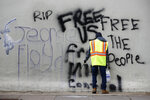 A worker removes graffiti from a building, Tuesday, June 2, 2020, in Washington, following protests over the death of George Floyd, who died after being restrained by Minneapolis police officers. (AP Photo/Patrick Semansky)