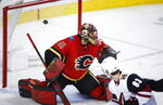 Arizona Coyotes' Conor Garland, right, scores on Calgary Flames goalie Mike Smith during second period NHL hockey action in Calgary, Alberta, Monday, Feb. 18, 2019. (Jeff McIntosh/The Canadian Press via AP)