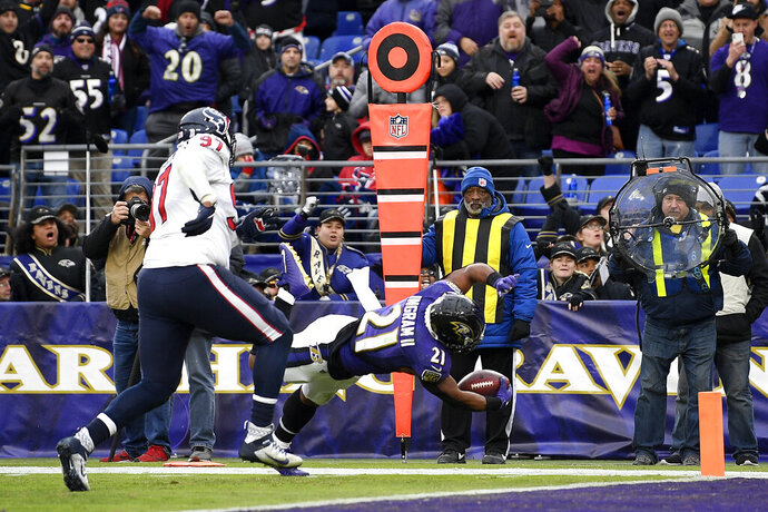 Baltimore Ravens running back Mark Ingram (21) dives in for a touchdown on a pass from quarterback Lamar Jackson, not visible, during the second half of an NFL football game against the Houston Texans, Sunday, Nov. 17, 2019, in Baltimore. (AP Photo/Nick Wass)