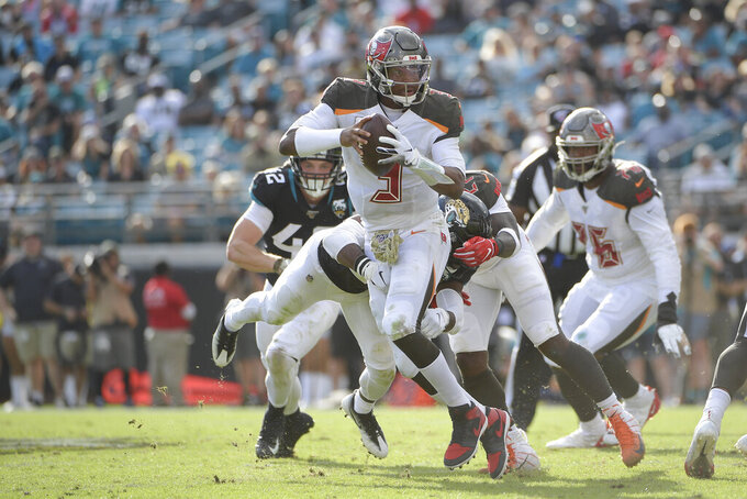 Tampa Bay Buccaneers quarterback Jameis Winston, center, scrambles from the pocket during the second half of an NFL football game against the Jacksonville Jaguars, Sunday, Dec. 1, 2019, in Jacksonville, Fla. (AP Photo/Phelan M. Ebenhack)